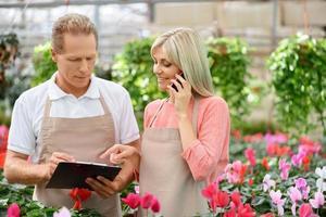 trevliga blomsterhandlare som arbetar i växthuset foto