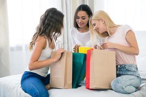tre flickvänner med många shoppingväskor foto