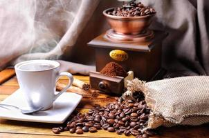 sammansättning med en kopp kaffe, bönor och kaffekvarn foto