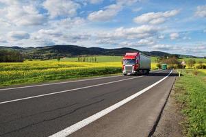 röda och gröna lastbilar på vägen mellan rapsfält