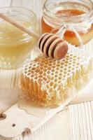 honung i burken med honungskaka och träsked foto