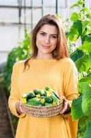 vacker kvinna med en korg med gurkor foto