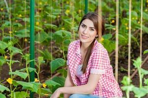vacker ung kvinna trädgårdsskötsel och ler mot kameran. foto