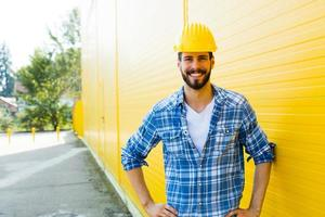 vuxen arbetare med hjälm på gul vägg foto