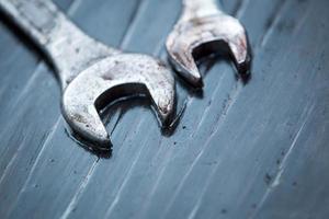 skiftnyckelverktyg med daggdroppe ovanpå träbord foto