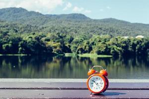 röd väckarklocka med två klockor på trägolvet foto