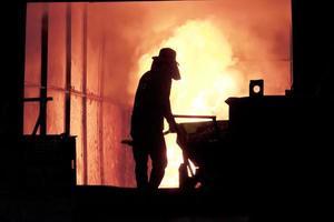 man som arbetar i det stänkande smält järn - lagerbild foto