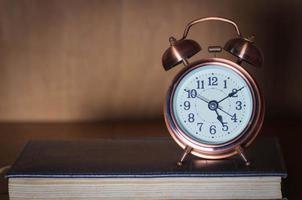 väckarklocka och bok. foto