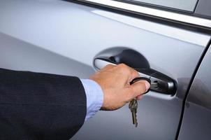 man sätter bilnyckeln i dörrlåset foto