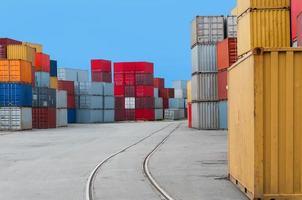 container i en hamn med järnvägsspår foto