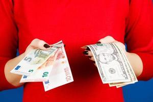euro och dolar i händerna på en flicka foto