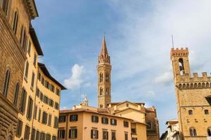 klocktornet i Palazzo del Bargello och kyrkespiren foto