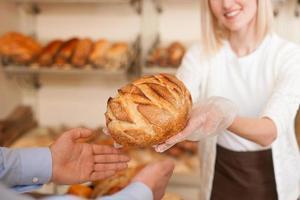 den skickliga kvinnliga bagaren säljer färsk bakelse foto