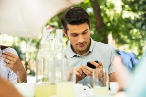 man använder smarttelefonen medan han sitter i utomhusrestaurangen foto