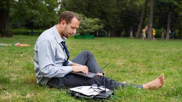 affärsman som sitter på ett gräs med bärbar dator. foto