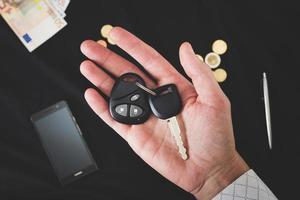 bilnycklar på den manliga handflatan foto