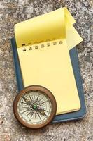 vintage kompass och tom gul anteckningsblock foto