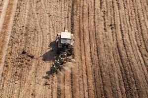 Flygfoto över traktor som plogar fältet foto