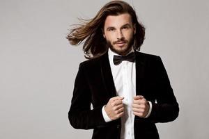porträtt av stilig snygg man i elegant svart kostym foto