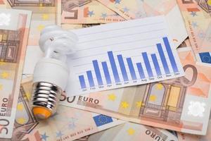 energibesparande glödlampa och graf på eurosedlar foto