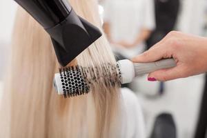 professionell kvinnlig frisör arbetar med hårtorkare foto