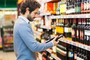 man i en stormarknad som väljer vinflaska foto