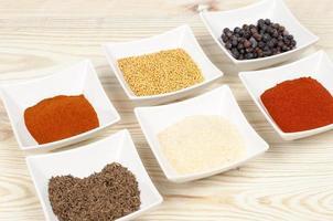 olika kryddor på träbord foto