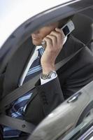 affärsman som använder mobiltelefonen i bilen foto