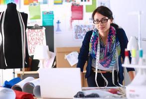 vacker modedesigner som står i studio foto