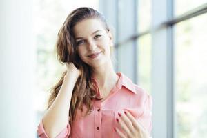 vacker affärskvinna som håller håret och ler foto