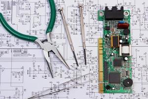 tryckta kretskort och precisionsverktyg på diagram över elektronik foto
