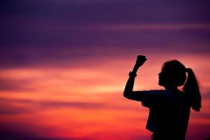 silhuett av framgångsrik kvinna med armen upp. foto