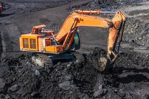 laddar gruvtruckar en grävmaskin foto