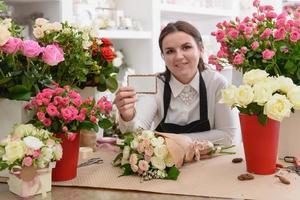 kvinnlig blomsterhandlare som visar visitkort bland buketter i blomsterbutiken foto