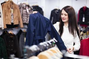 kvinna som väljer jacka i butiken foto
