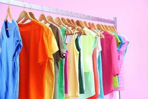 olika kläder på galgar, på rosa bakgrund foto