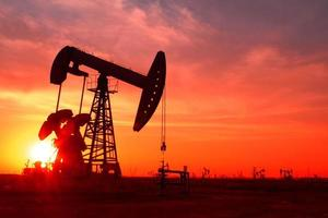 en silhuett av en oljepump i ett oljefält vid solnedgången foto