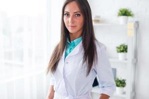 porträtt av ung kvinna läkare med vit kappa stående i foto