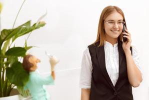 vacker flicka i receptionen som svarar på samtalet foto