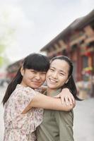 två unga kvinnor som omfamnar foto