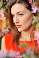 stående vacker flicka på bakgrund blommande träd foto