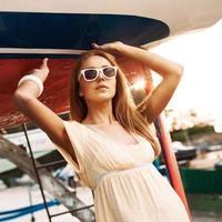 vacker flicka i sommarklänning på havsbryggan foto