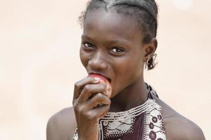 hälsosymbol: vacker ung afrikansk flicka som biter ett sunt äpple foto