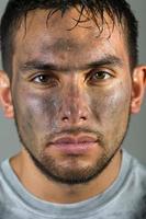 närbild latinamerikansk man med smutsigt ansikte ser rakt in i kameran foto