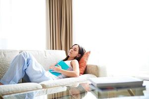 kvinna som sover i soffan med boken. foto