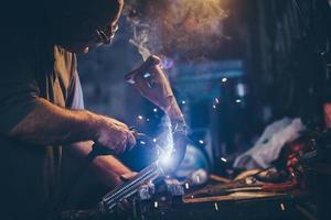 hantverkare svetsar stål.retrofilter, spannmål tillagd. foto