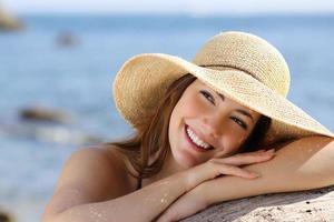 glad kvinna med vitt leende tittar i sidled på semester foto