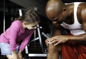 liten flicka och atletisk man sätter på sig bandhjälp foto