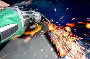 tung industriarbetare skärande stål med vinkelslipare foto