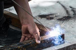 arbetare svetsar stål med gnistorbelysning foto